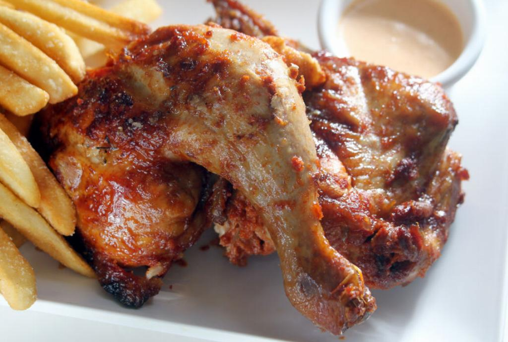 Saucy chicken sits on a plate with fries and dipping sauce.