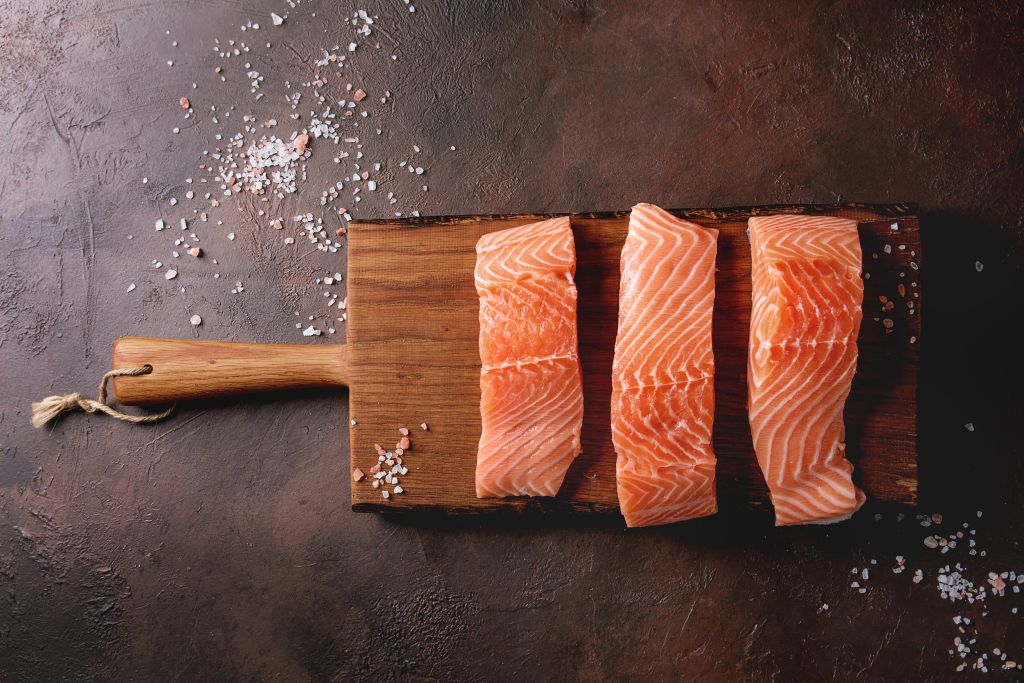 Raw salmon filets rest on a wooden board.