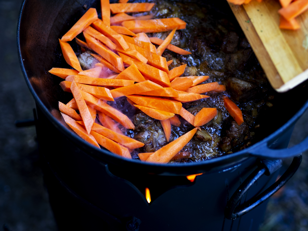 Chopped carrots are added to a lamb strew.