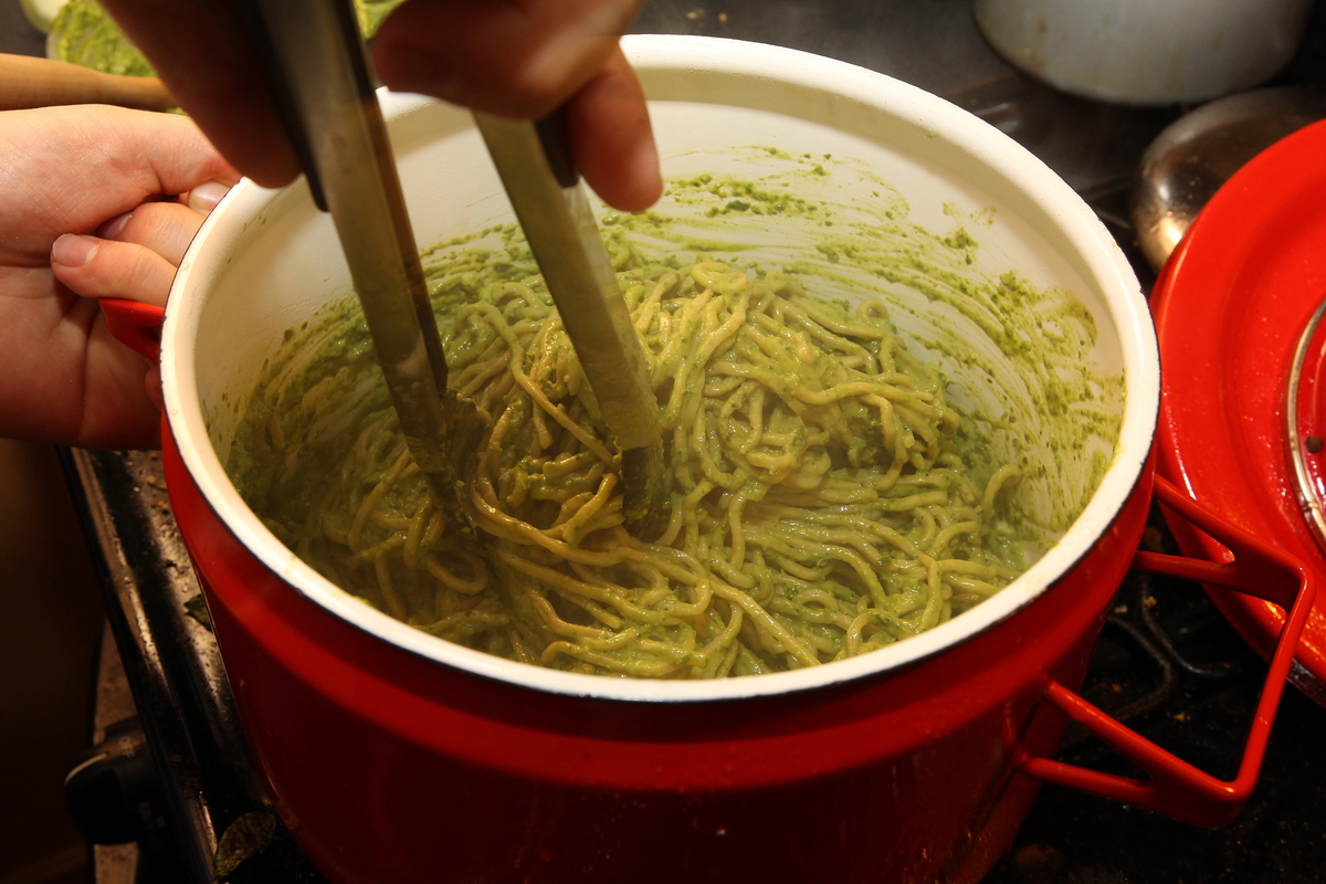 Pesto sauce is being cooked into a pot of spaghetti noodles.