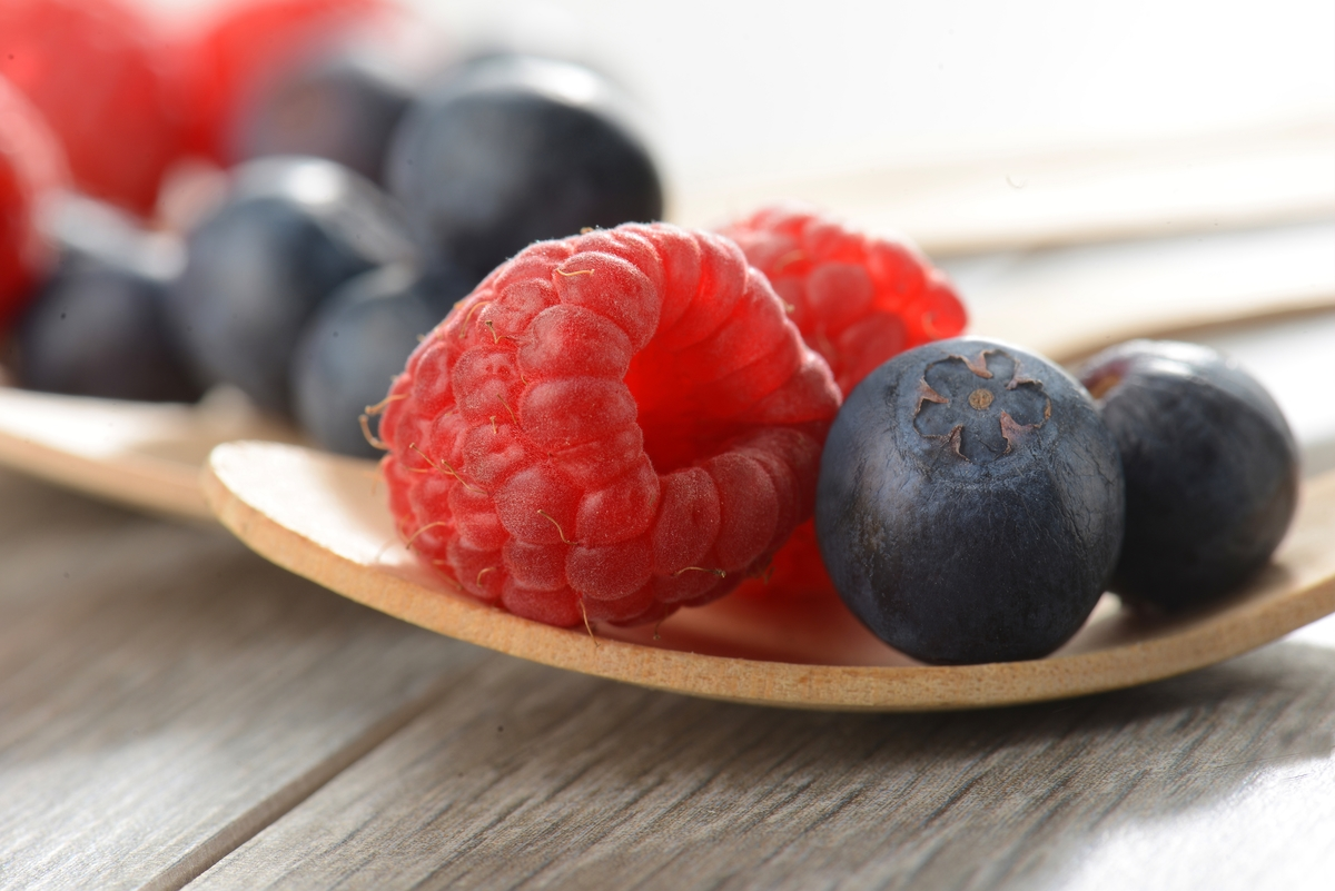 A small wooden plate holds raspberries and blueberries.