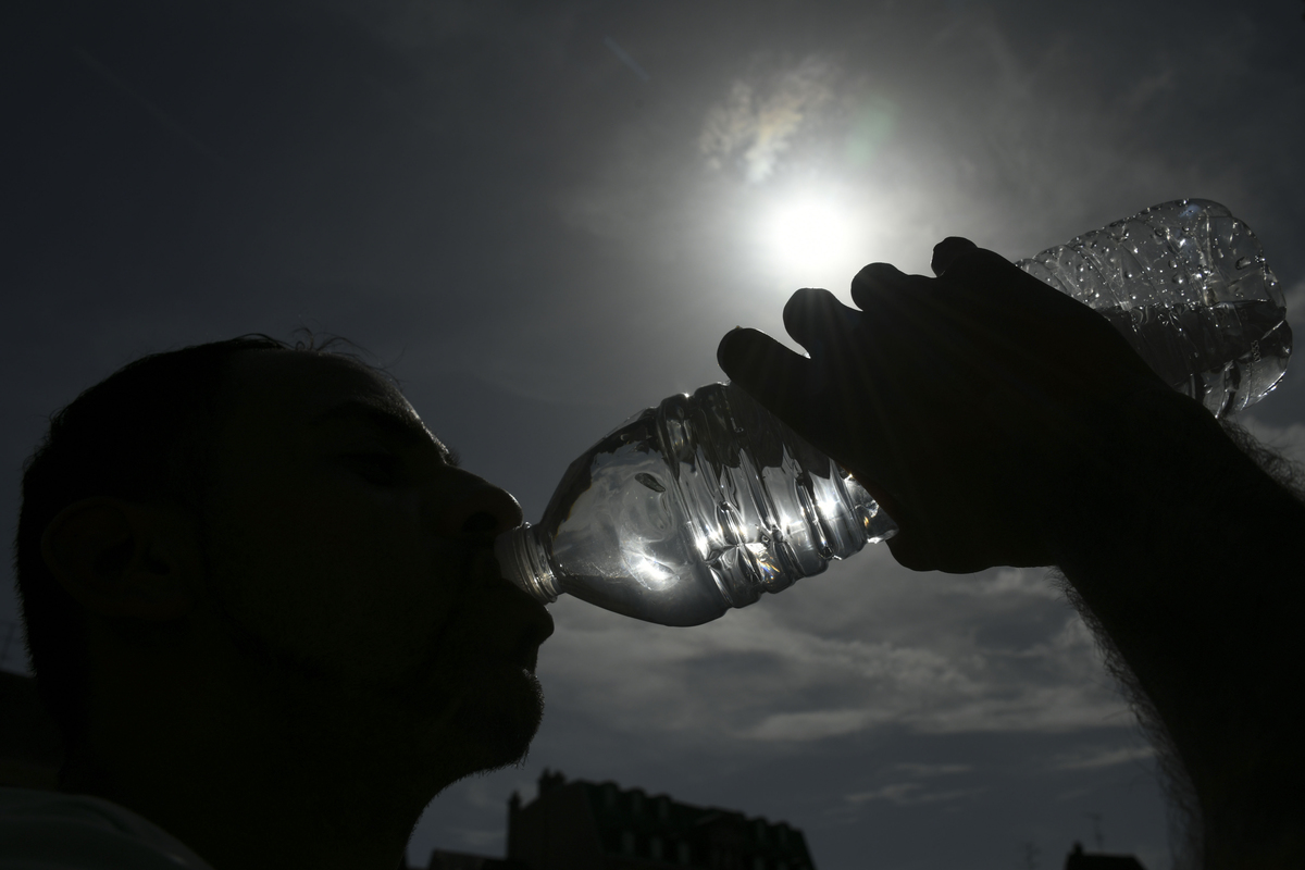 A person drinks water from a plastic water bottle.