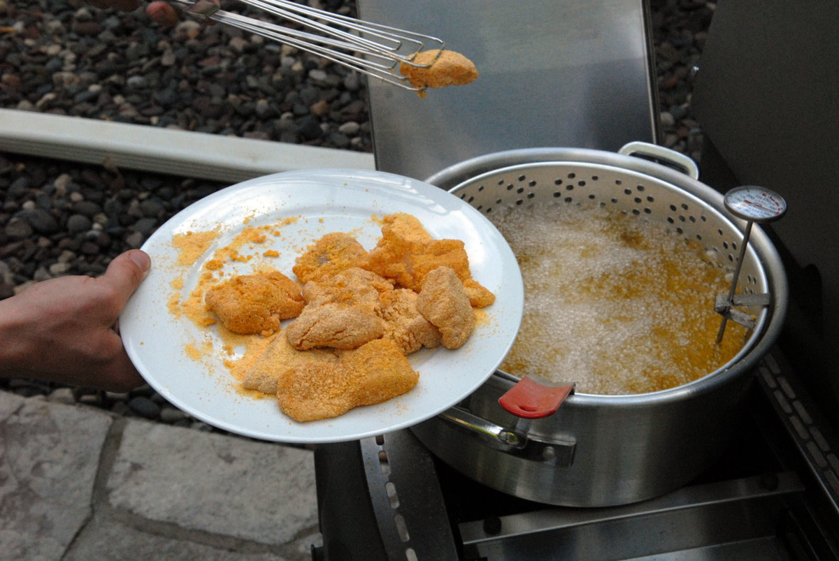 A person removes fried fish fillets from a frying pan.