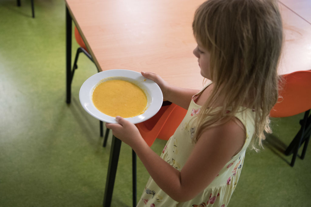 A young girls carries a bowl of soup.
