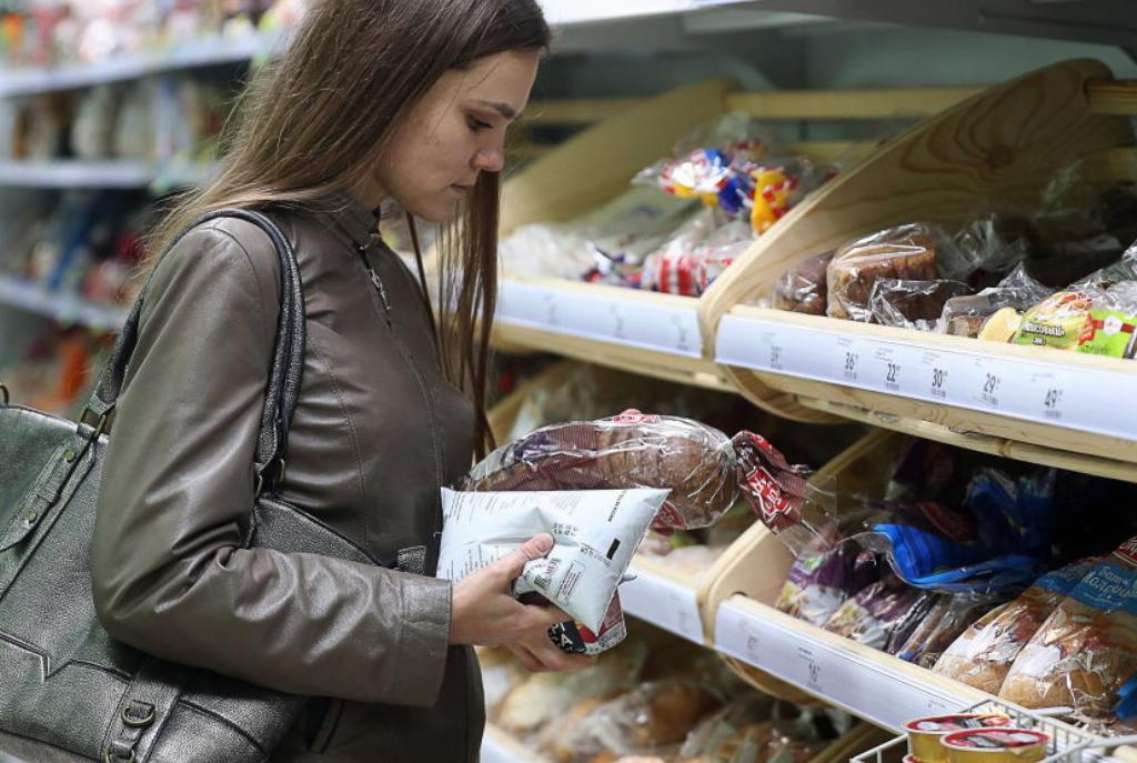 A woman shops for bread at a store.