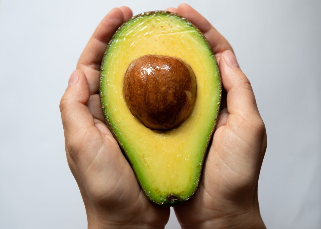 A woman holds one half of an avocado between her hands.