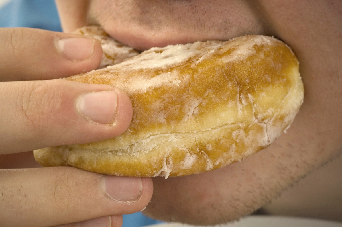 Close-up of man eating jam donut.