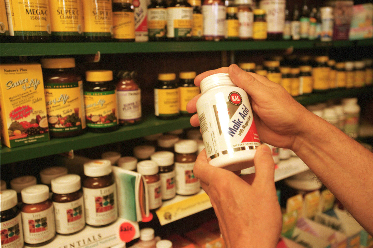A customer looks at vitamins in a store.