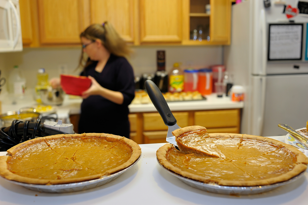 Two pumpkin pies sit on the kitchen counter as a woman prepares a dish.