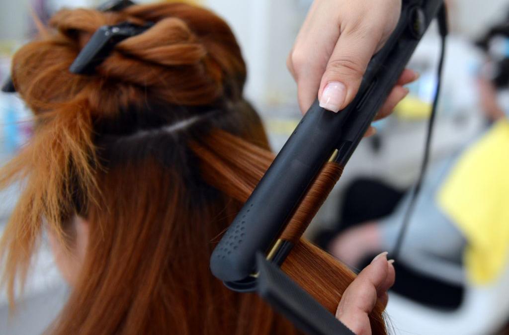Woman straightening client's hair