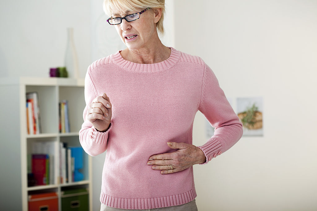 A woman wears a look of discomfort while placing a hand to her abdomen.