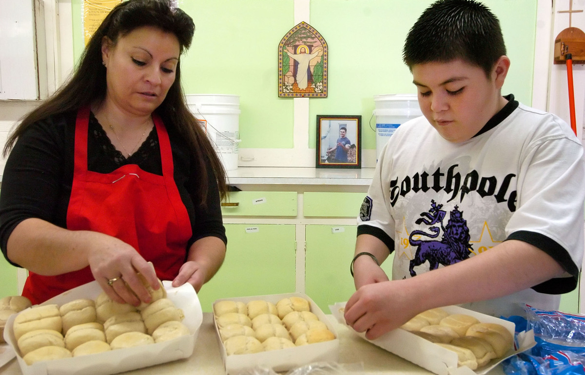 Judy Padilla , left, butters rolls with her grandson, Santino Padilla.