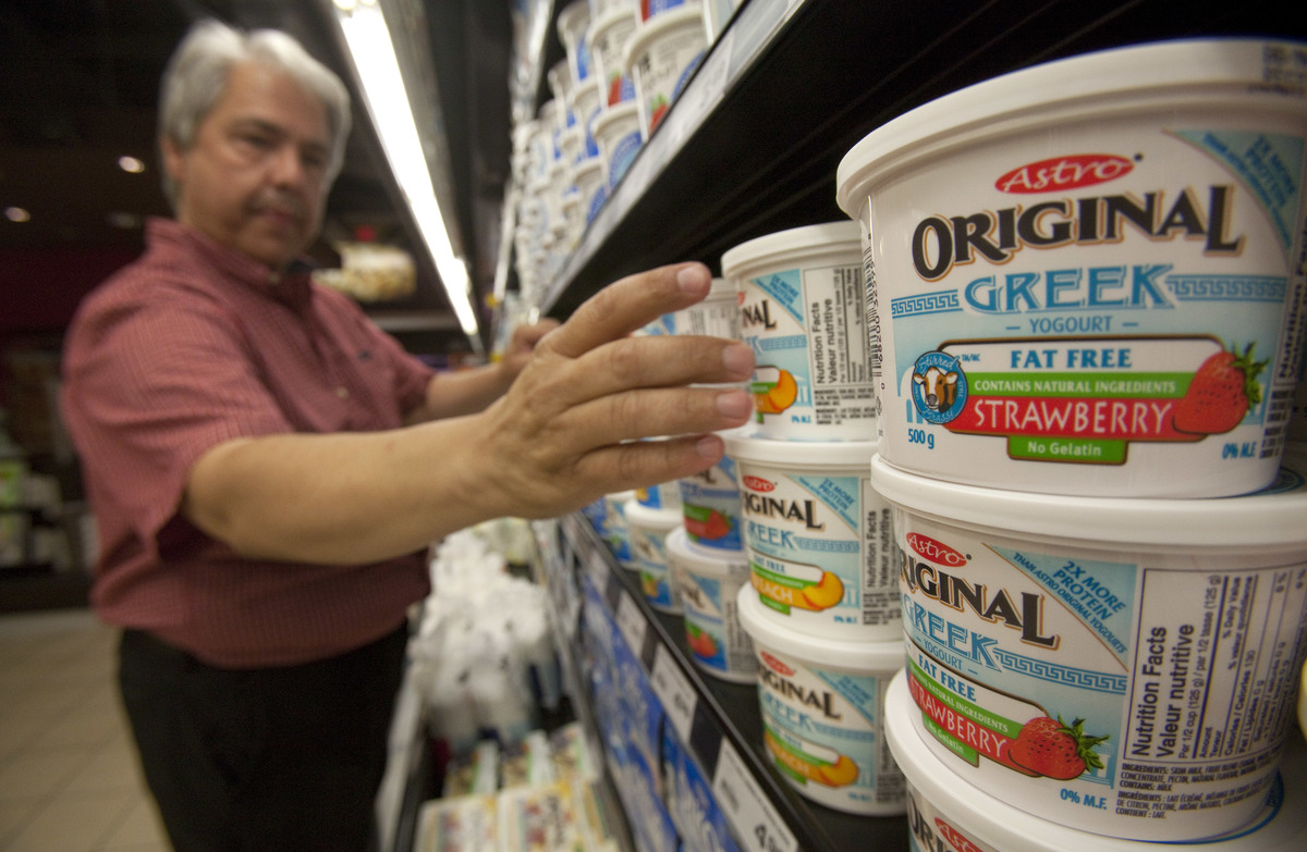 Dairy manager stocks Greek yogurt at a grocery store.