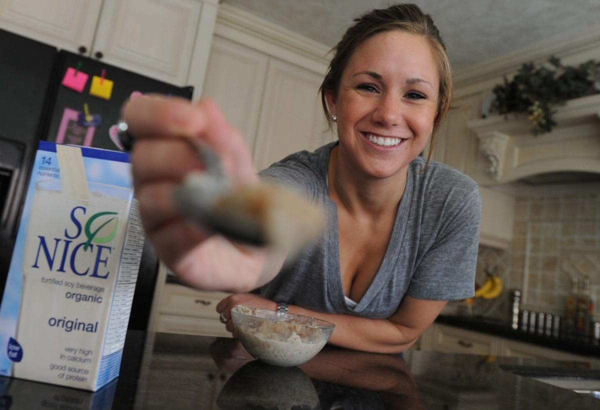 Woman holds out a spoonful of instant oats.