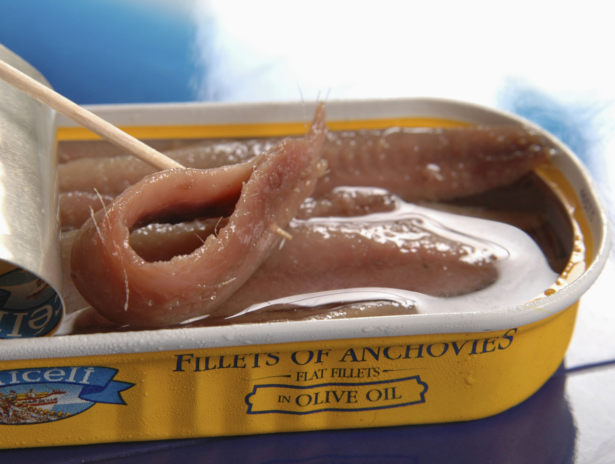 Anchovie fillets soaked in olive oil are in a can.