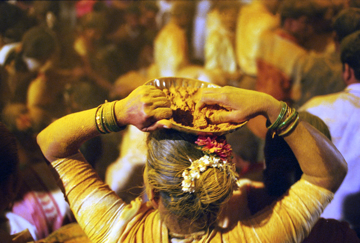 Woman at a Hindu festival throws powdered yellow turmeric and chunks of coconut over revellers from a basket on her head.