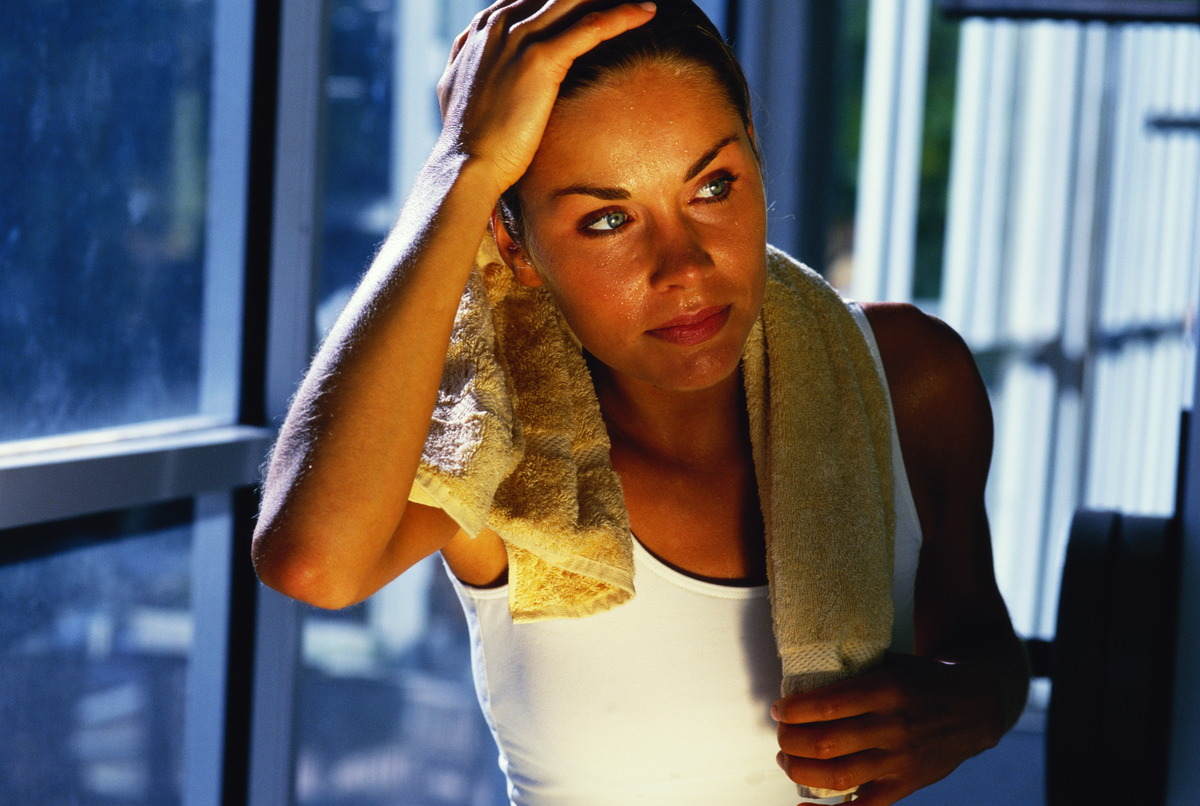 A woman drapes a towel over her shoulders after exercising at the gym.