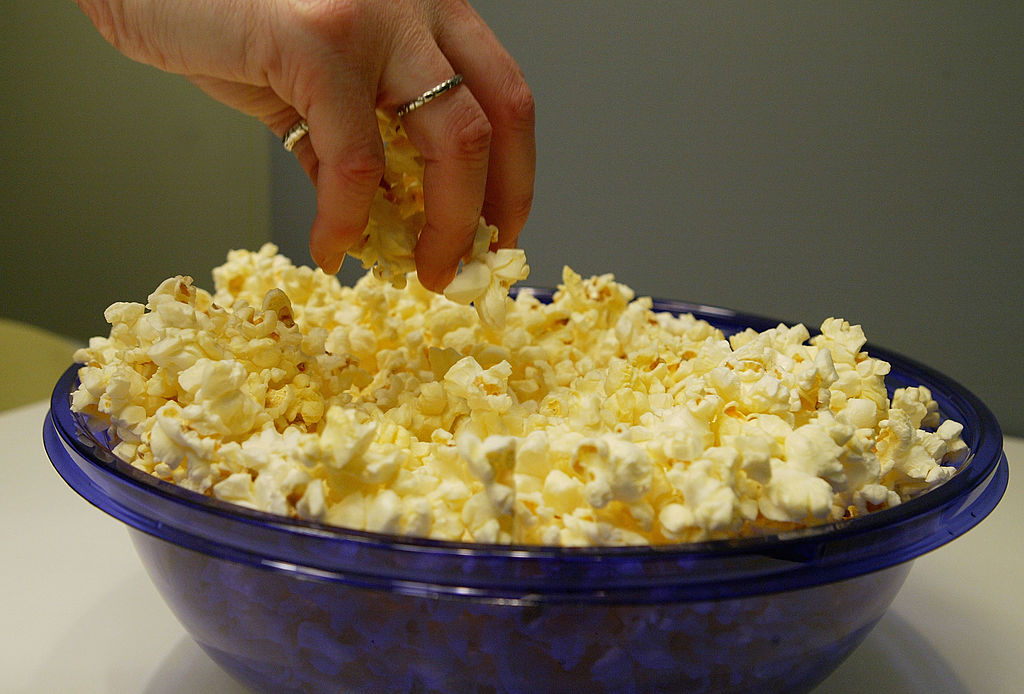A woman grabs popcorn from a bowl.