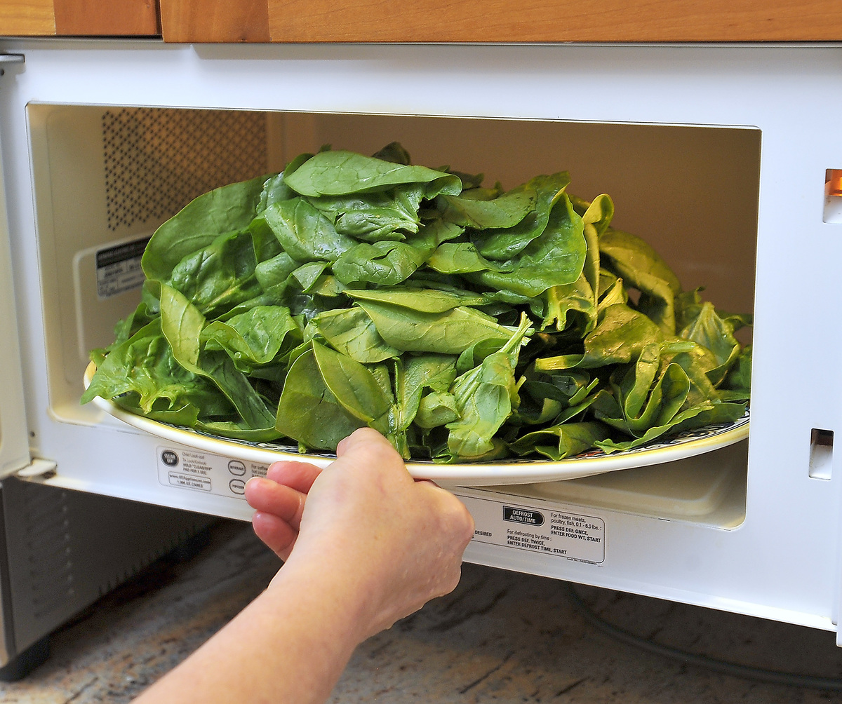 Woman puts a plate of fresh young spinach into the microwave to wilt.