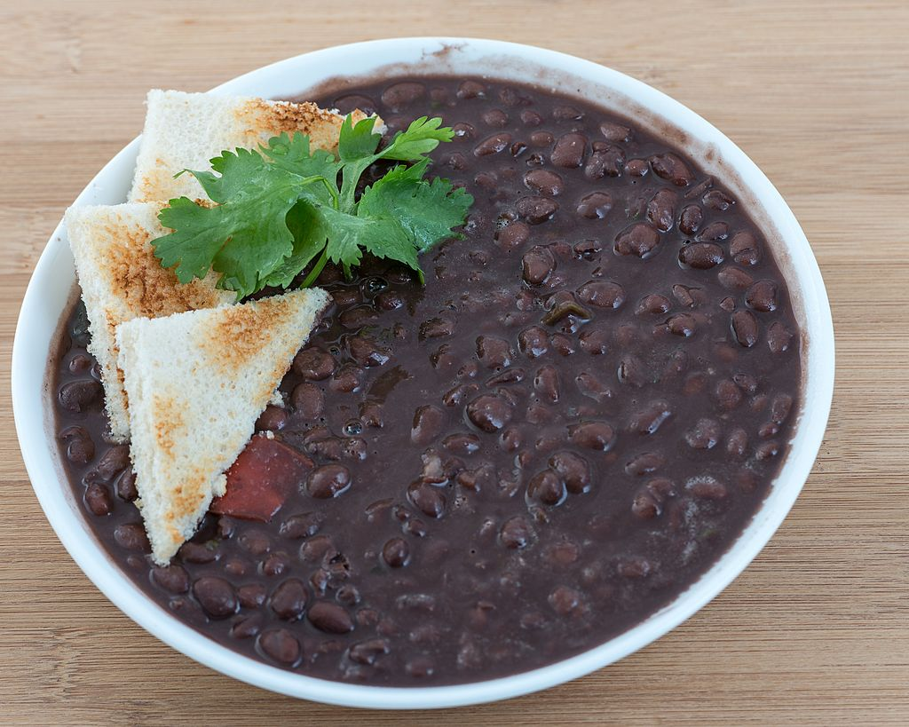 A bowl of blacks beans is dressed with dry toast and cilantro.