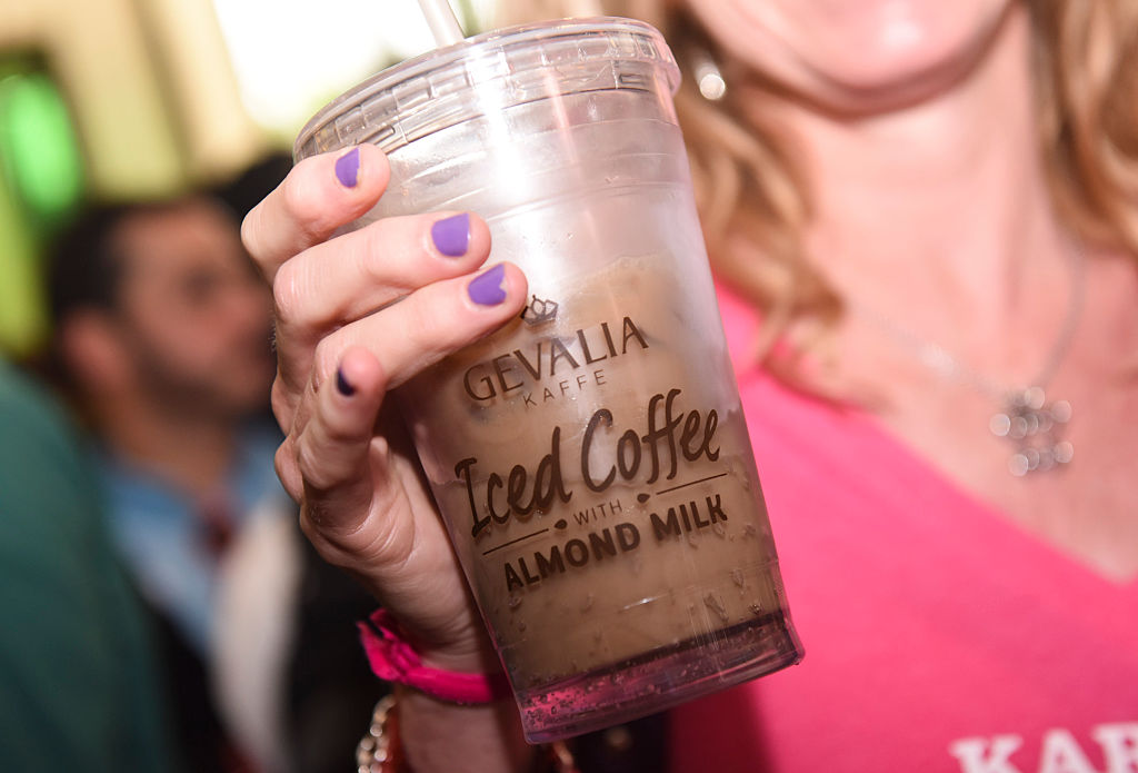A woman hold a container full of almond milk iced coffee.