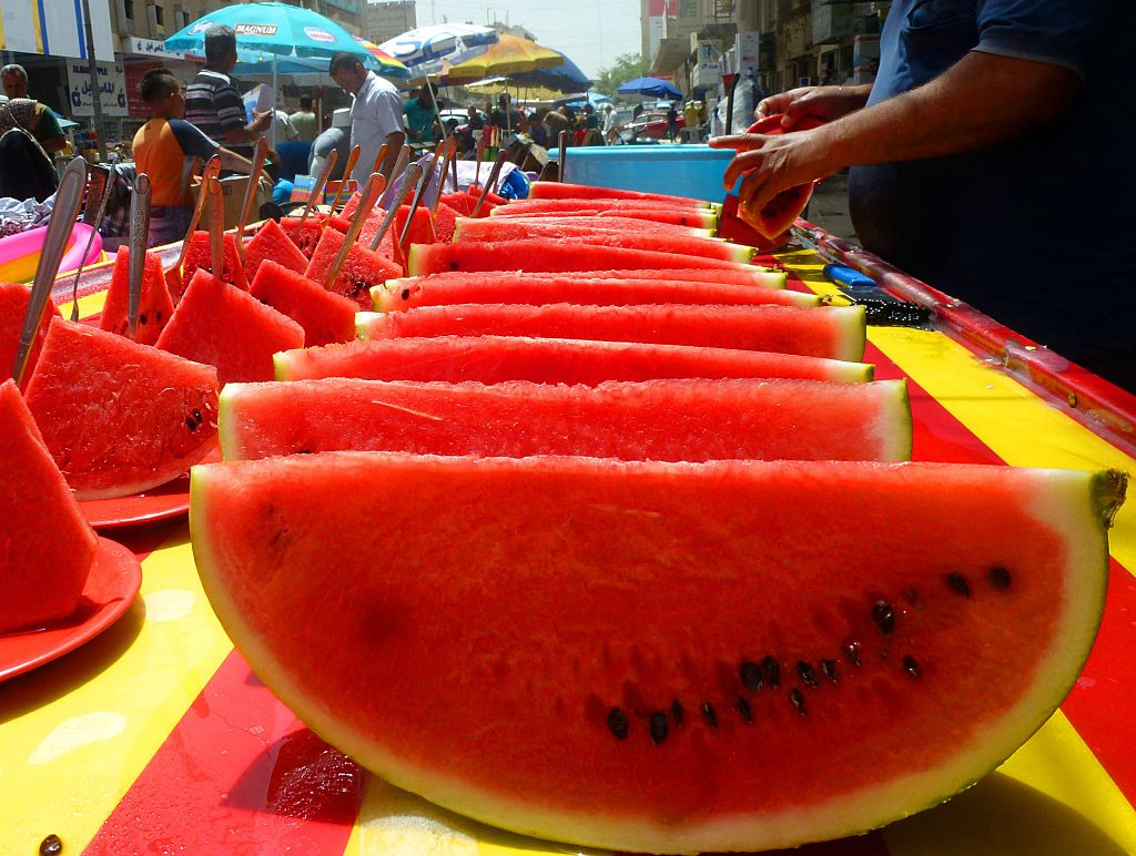 A vendor sells large pieces of watermelon on the street.