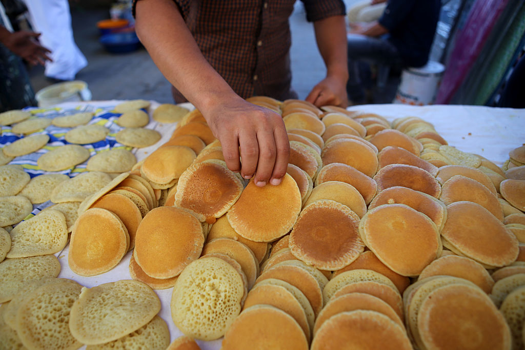 A boy grabs a pancake from a large pile of them laid out on a table.