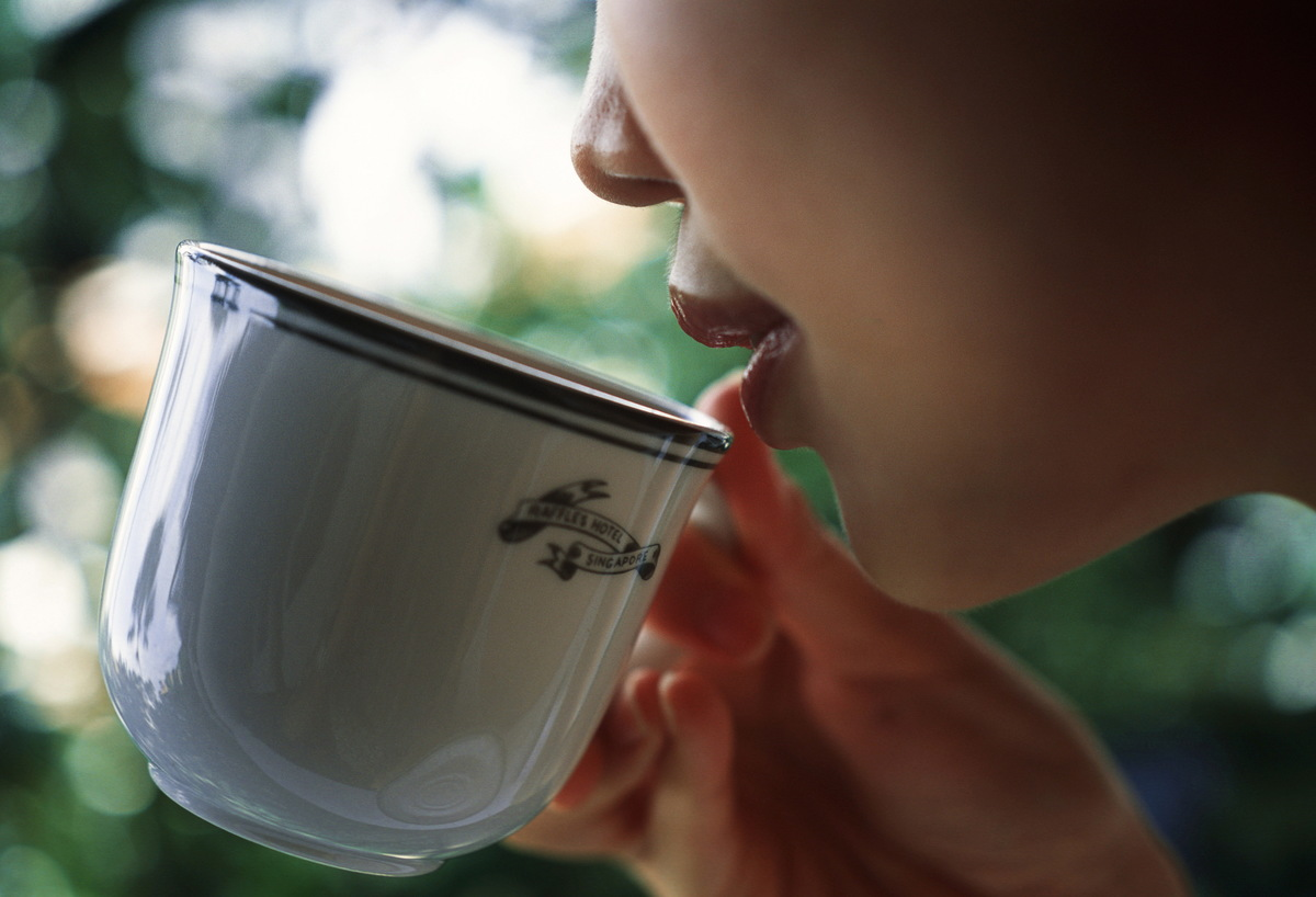 A woman delicately sips from a cup of coffee.
