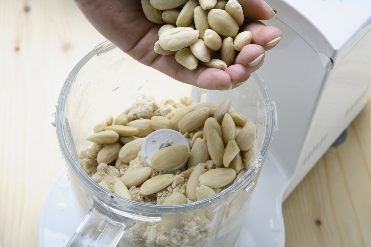 A woman placed peeled almonds in a blender to create a crumble.
