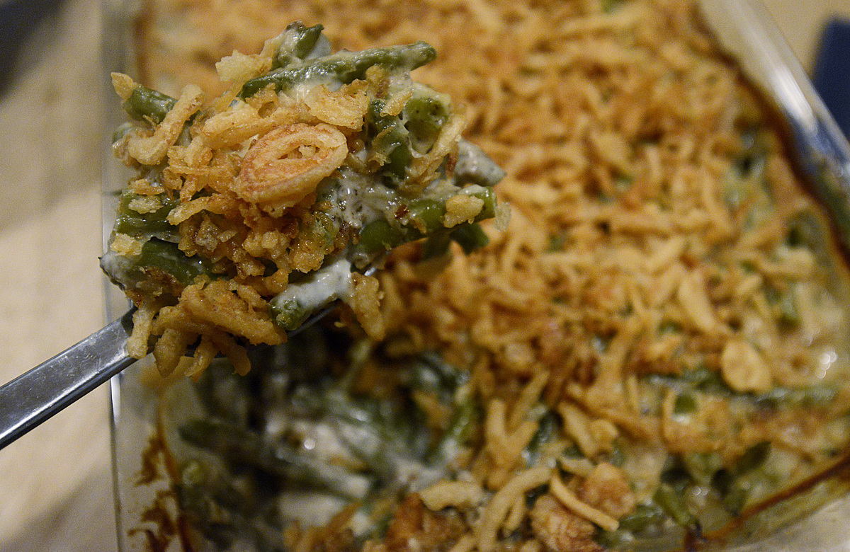 Person removes a spoonful of green bean casserole from a pan.