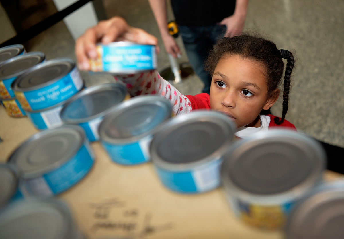 A girl reaches for a tuna can on a shelf.