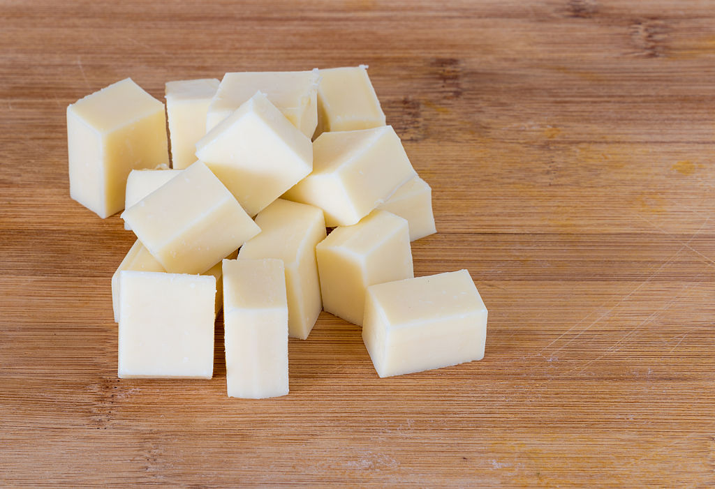 Cubed cheese sits on a wooden table.