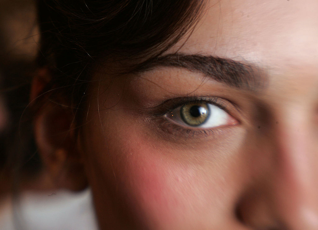 A close-up shows a woman's green eye.