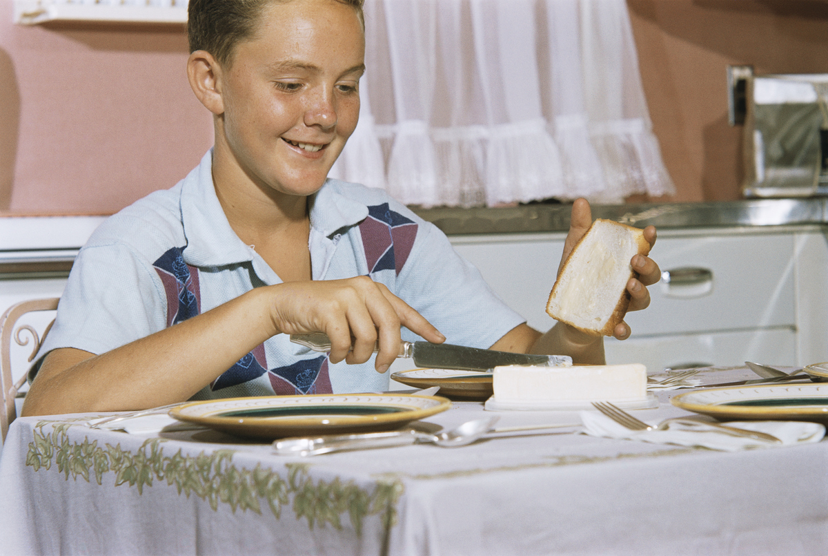 A boy spreads butter on white bread.