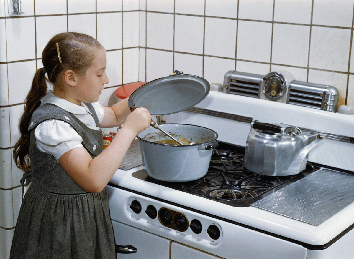 Girl stirs a pot of cooking soup in the kitchen.