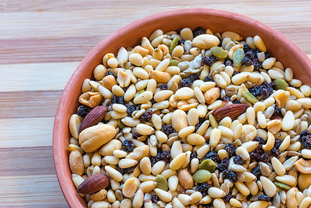 A bowl of nuts, seeds, and dried fruit sits on a wooden surface.