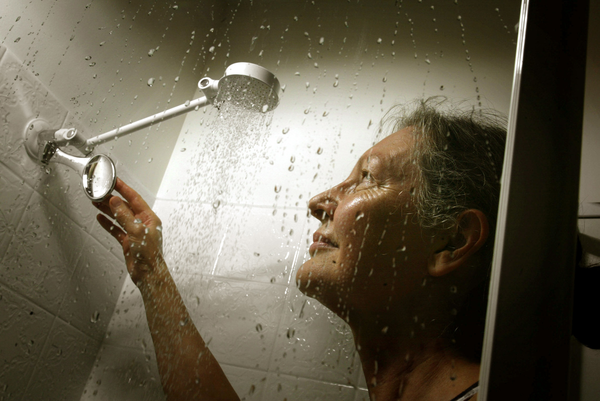 A woman looks up at her running shower.