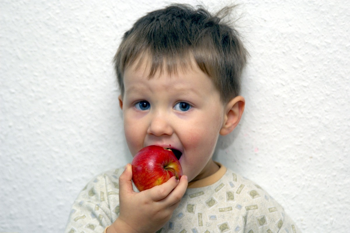 A young boy eats an apple against a white wall.
