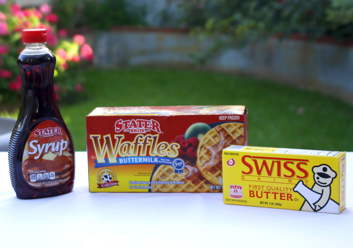 Stater Bros Frozen Waffles, maple syrup, and Swiss Butter are on a table outdoors.