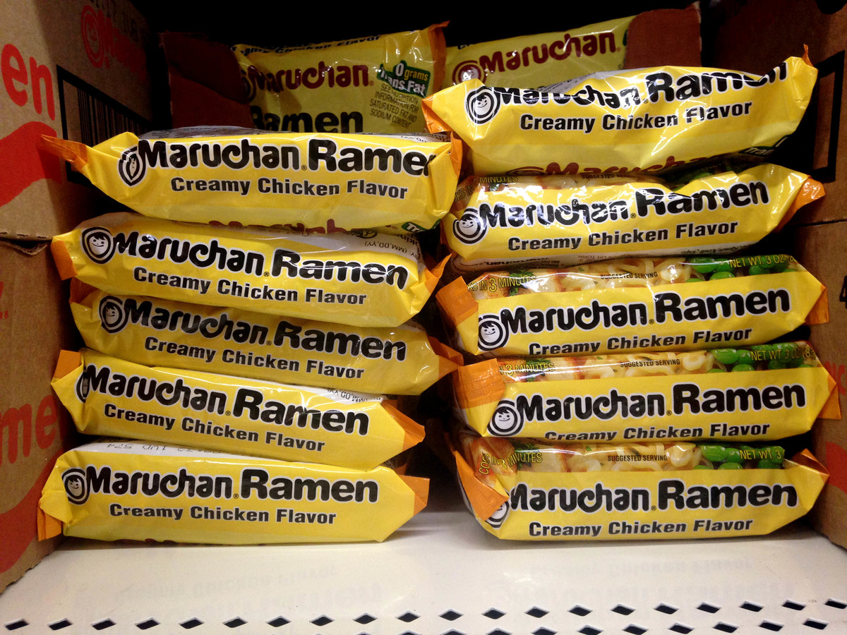 Dried ramen noodle packages are stacked on a store shelf.