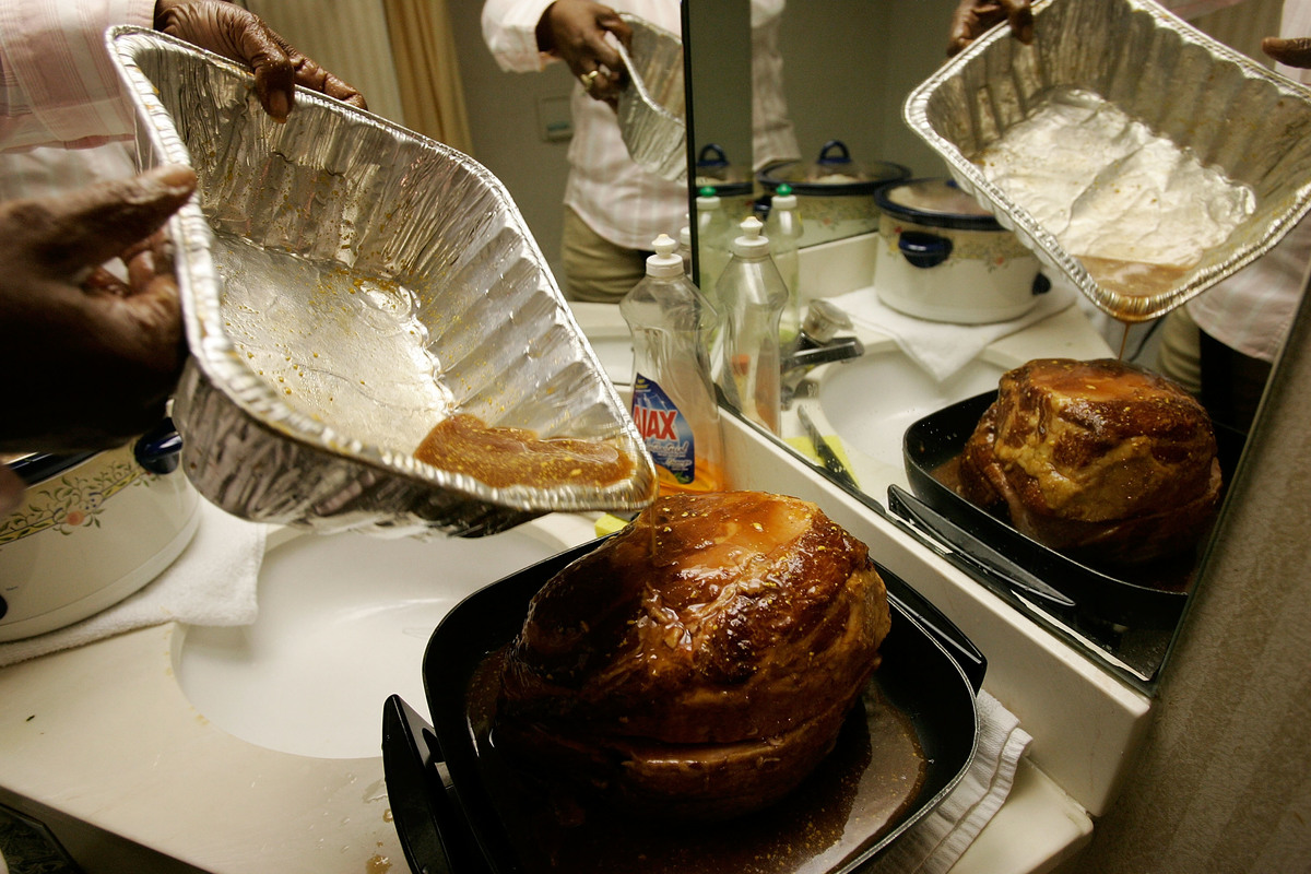 Kathy Curry of New Orleans puts glaze on a ham as she prepares her Thanksgiving dinner in the bathroom of her hotel room.