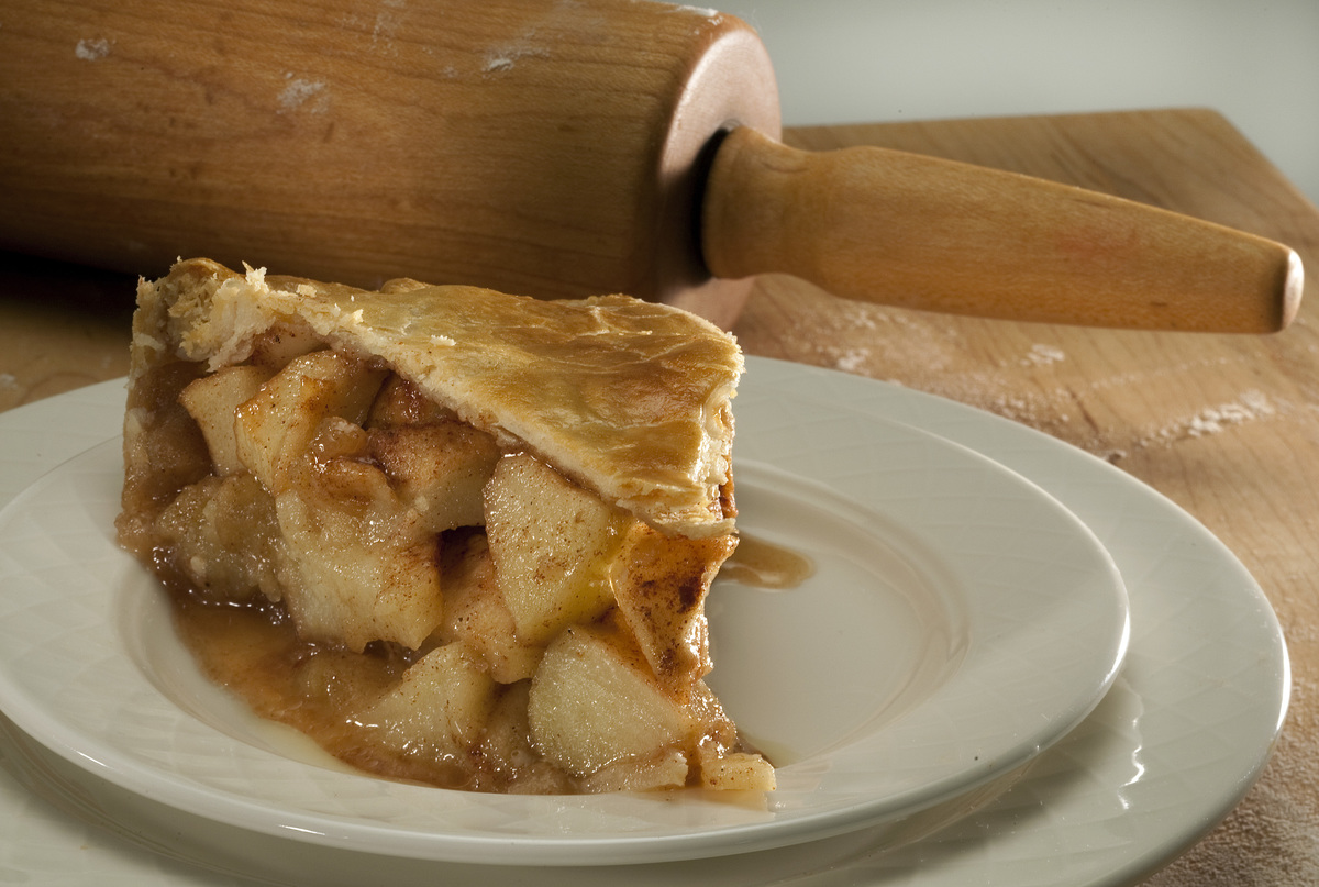 A slice of apple pie sits on a plate in front of a rolling pin.