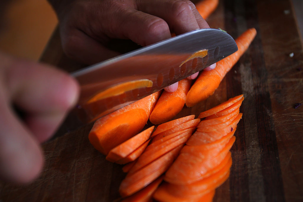 A woman chops carrots.