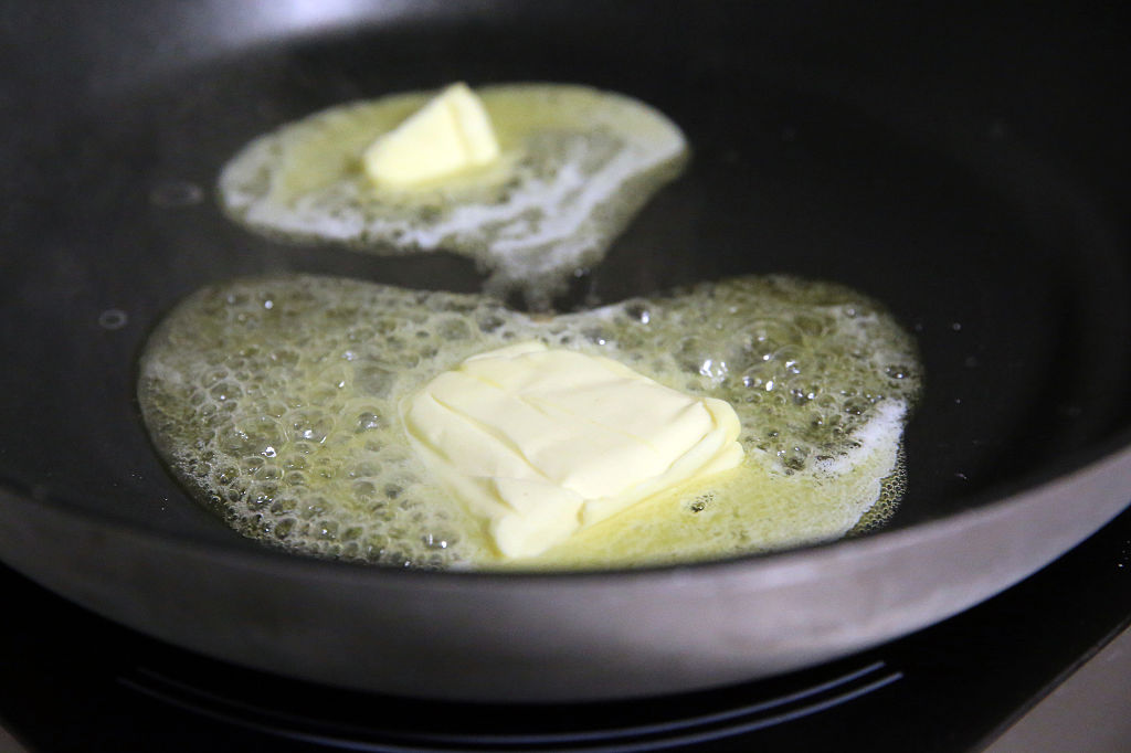 Butter melts in a skillet.