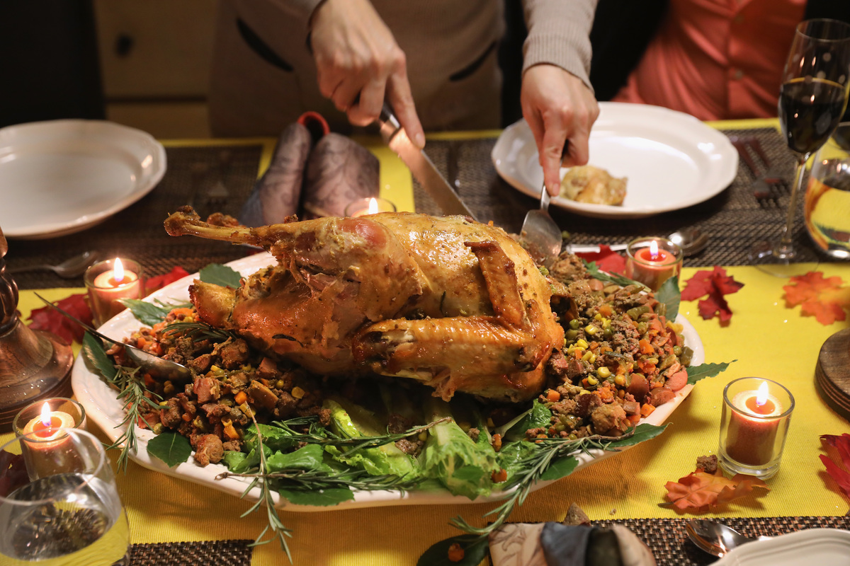 A person carves the Thanksgiving turkey on a dinner table.
