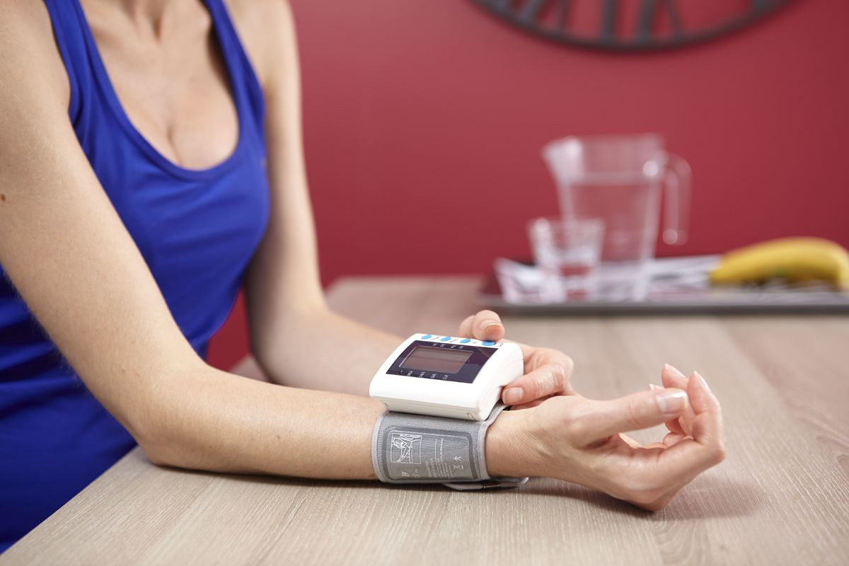 A woman measures her blood pressure at her kitchen table.