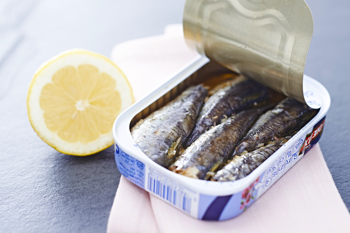 An open can of sardines sits next to a lemon.