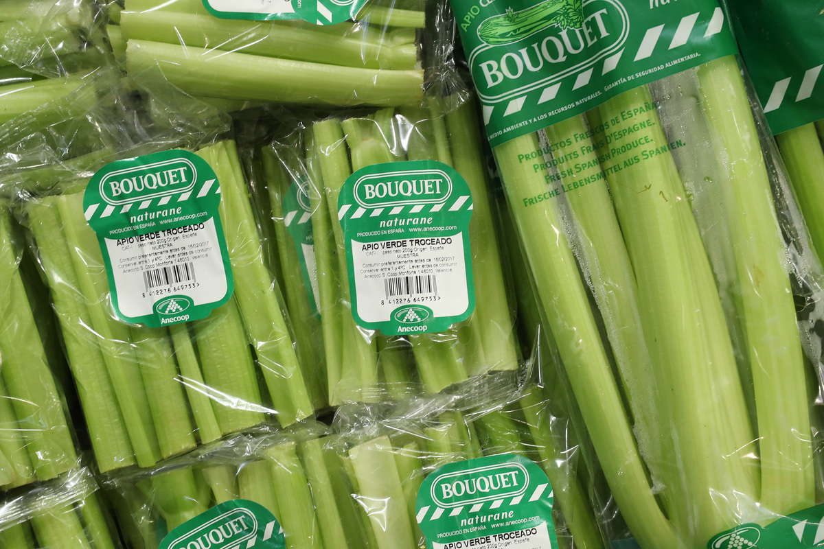 Bagged organic celery lies on display.