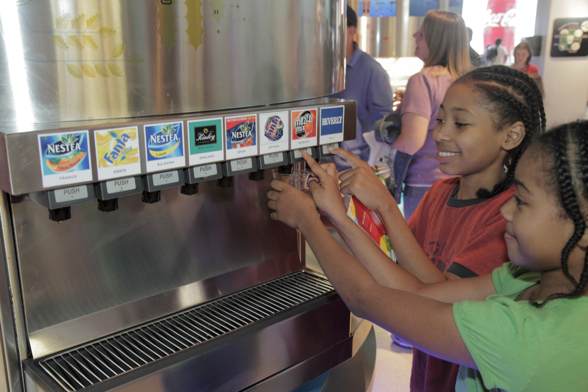 Two girls pour soda at the 'Taste It!' exhibit in the World of Coca-Cola.