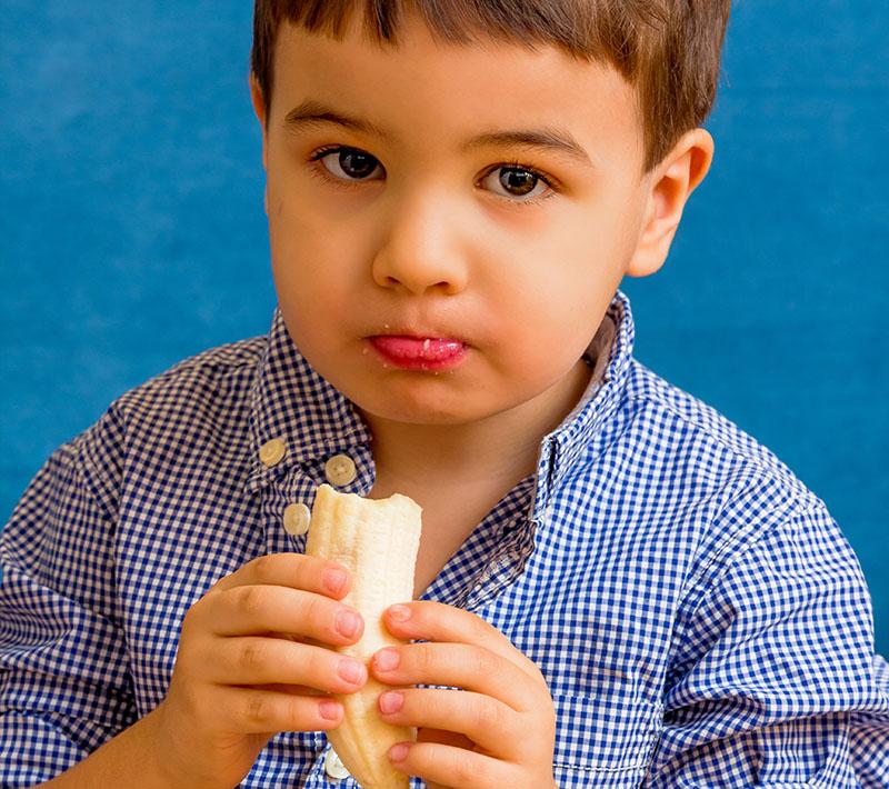 A toddler eats a banana.